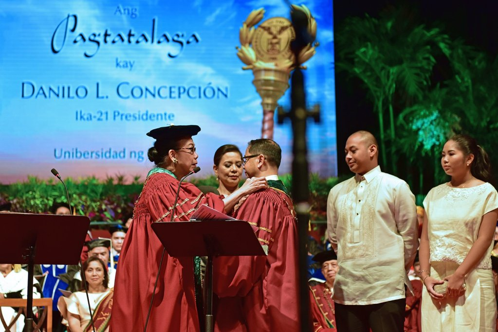 Commission on Higher Education and UP Board of Regents Chairperson Patricia Licuanan affixes the UP President's Medallion over President Concepción's academic gown with the assistance of Atty. Ma. Gabriela Roldan Concepción, the president's wife. Looking on are two of the four Concepción children. (Photo by Bong Arboleda, UP MPRO)