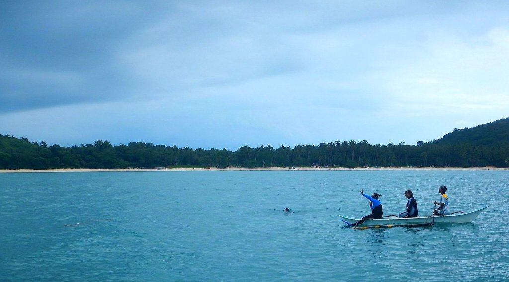 """Lem at the bow with Professor Helene Marsh, world-renowned dugong expert and his PhD adviser, recently off Calauit Island, Palawan, """"acclimatizing"""" a dugong (partially seen) for underwater observation. Photo courtesy of the UPD-IESM Marine Mammal Research and Stranding Laboratory"""