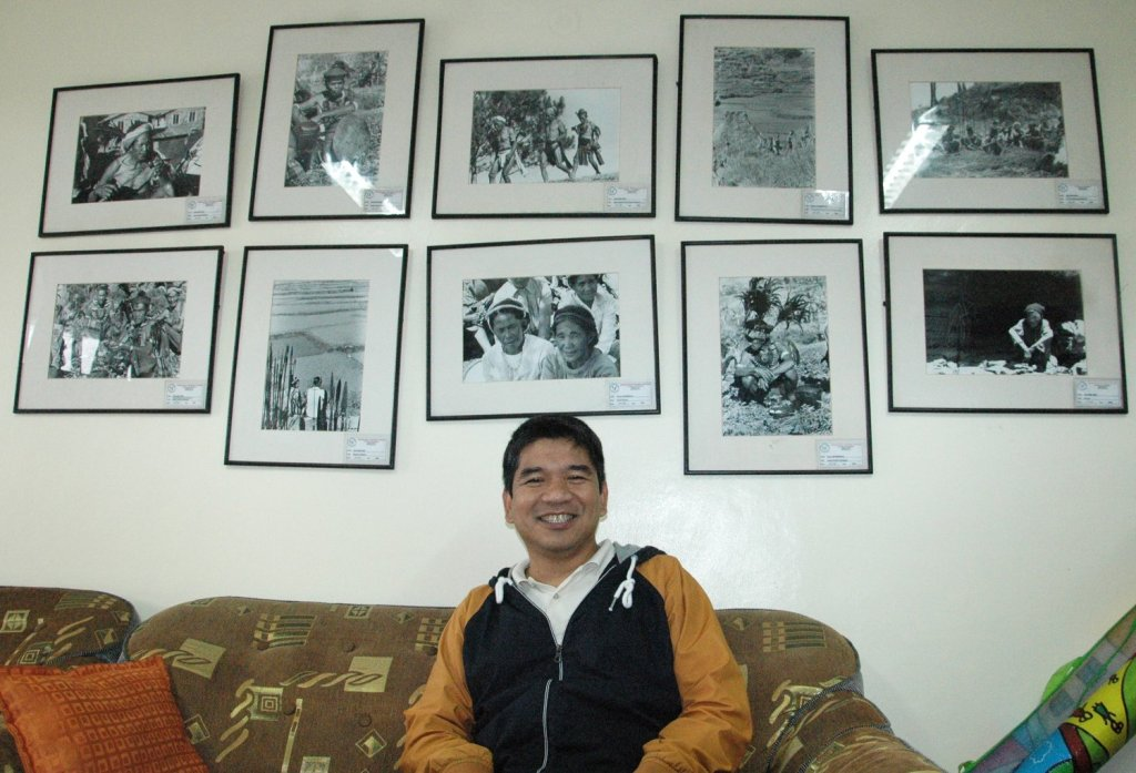 Dr. Wilfredo V. Alangui, professor of Mathematics at the Department of Mathematics and Computer Science, College of Science, UP Baguio, sitting underneath a photo gallery of indigenous people in his office. (Photo by Celeste Llaneta, UP MPRO)