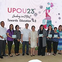 UP President Danilo Concepcion (fifth from left) and Chancellor Melinda Bandalaria (to his left) pose for photos with representatives of some of UPOU's partner institutions. From left, with plaques: Tuntungin-Putho Integrated National High School; Quezon Power Limited Co.; HealthServ Los Baños Medical Center; CoopHub; Department of Science and Technology-Philippine Council for Industry, Energy and Emerging Technology Research and Development; Municipal Government of Mauban, Quezon; Veterans Bank; Land Bank of the Philippines; Los Baños Doctors Hospital and Medical Center, Inc.; and Digital Freedom Network (Photo by Misael Bacani, UP MPRO)