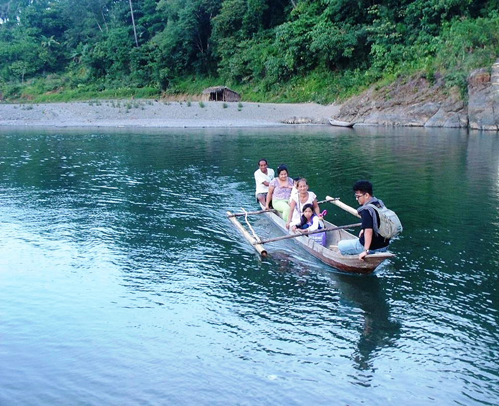 A Pahinungod volunteer immersing with a family in Nakar, Quezon, in 2014, tries out the family transport. (Photo courtesy of UPLB Ugnayan ng Pahinungod)