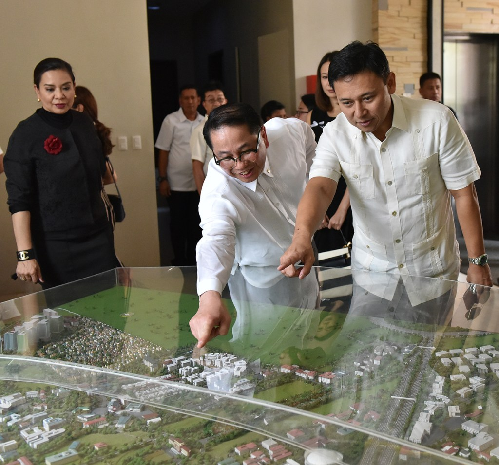 """UP President Danilo Concepcion shows Senator Juan Edgardo """"Sonny"""" Angara the scale model of the Diliman campus as Atty. Gabriela Concepcion looks on. The younger Angara is a member of the College of Law Class of 2000. He was the first of the Angara family to arrive. (Photo by Abraham Arboleda, UP MPRO)"""