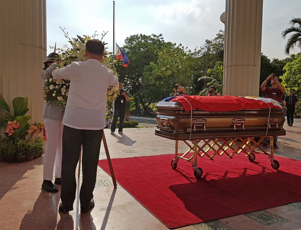 UP President Danilo Concepcion, assisted by a member of the UP Rayadillo, offers a wreath of white flowers beside Angara's casket. (Photo by Arlyn Romualdo, UP MPRO)