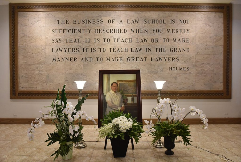 "SEJA's portrait stands in front of the Malcolm Theater before his remains arrive. In the background is a quote by former United States Supreme Court Justice Oliver Wendell Holmes Jr. inscribed in marble, greeting all who enter Malcolm Hall. ""The business of a law school is not sufficiently described when you merely say it is to teach law or to make lawyers. It is to teach law in the grand manner, and to make great lawyers."" This is the principle that has guided every faculty member, student, and alumnus of the College. (Photo by Abraham Arboleda, UP MPRO)"
