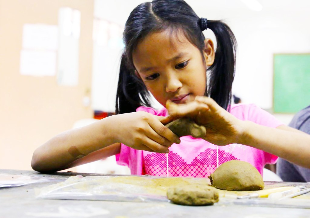 A child molding clay during the 2017 UP Baguio Summer Arts Festival. (Photo from the UP Baguio Summer Arts Program Facebook page)
