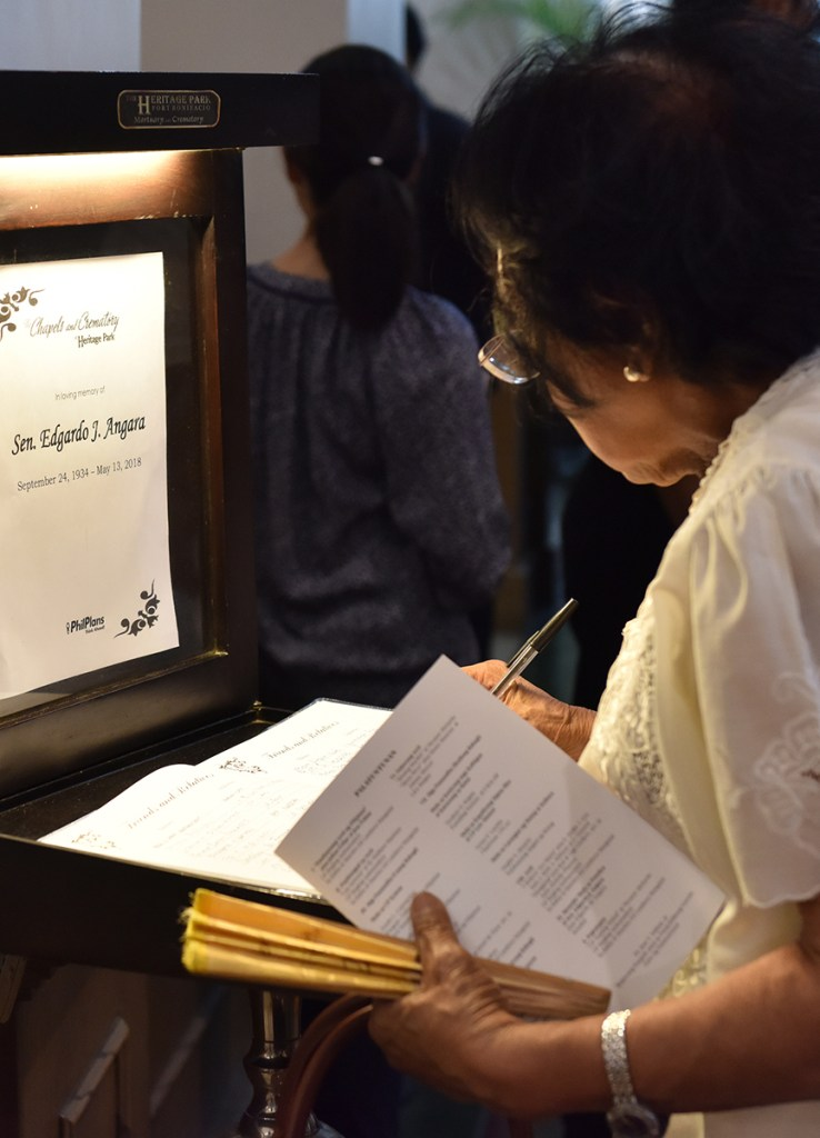 A visitor signs the guest book. (Photo by Abraham Arboleda, UP MPRO)