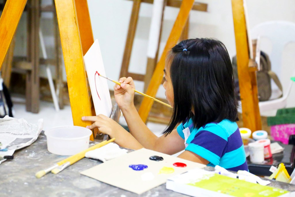 A child painting at an easle during the 2017 UP Baguio Summer Arts Festival. (Photo from the UP Baguio Summer Arts Program Facebook page)