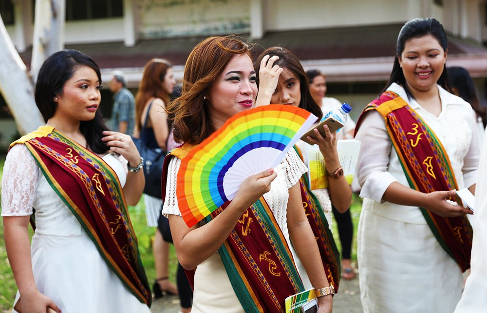 A rainbow-colored fan keeps this future grad cool under the mid-afternoon sun. (Photo by Misael Bacani, UP MPRO)