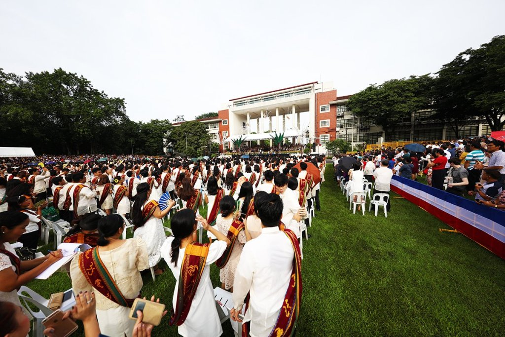 The candidates for graduation remain standing after the processional, their friends and families anticipating the start of ceremonies. (Photo by Misael Bacani, UP MPRO))