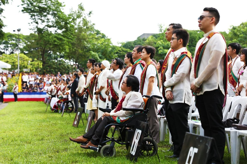 The candidates for graduation remain standing after the processional, their friends and families anticipating the start of ceremonies. (Photo by Misael Bacani, UP MPRO)