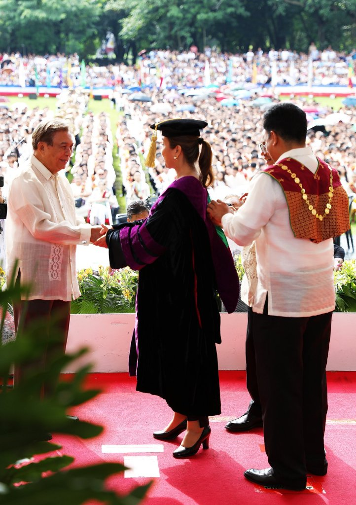 Sen. Loren Legarda is congratulated by her father after she receives the honorary Doctor of Laws. (Photo by Misael Bacani, UP MPRO)