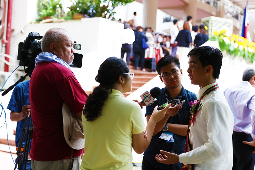 Ernest Delmo, BS Chemical Engineering, graduating summa cum laude with the highest GWA among his batch at 1.086, is interviewed by media upon alighting the stage. (Photo by Misael Bacani, UP MPRO)