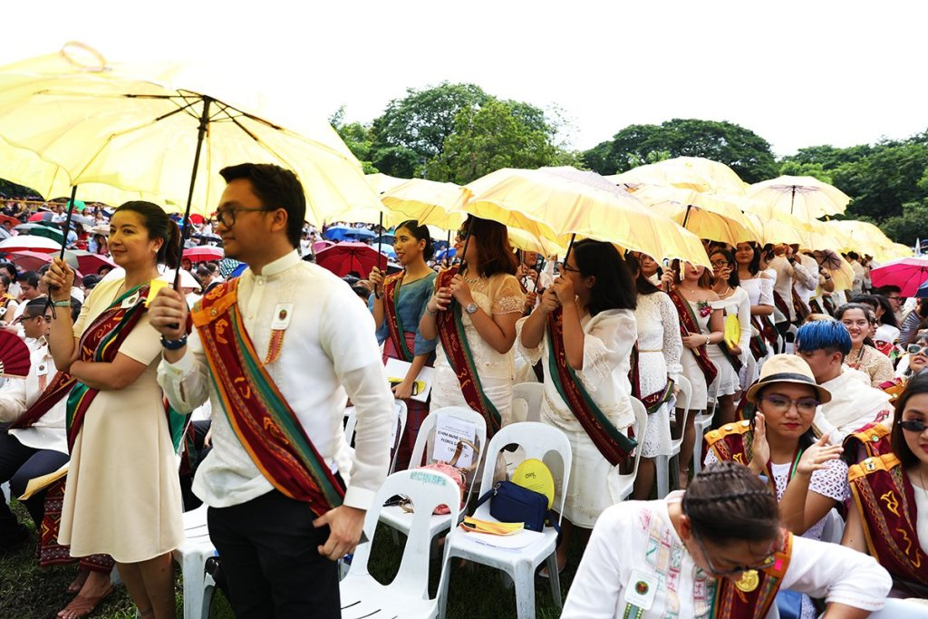 Candidates for graduation from the College of Mass Communication hold up uniform sunflower umbrellas. (Photo by Misael Bacani, UP MPRO)