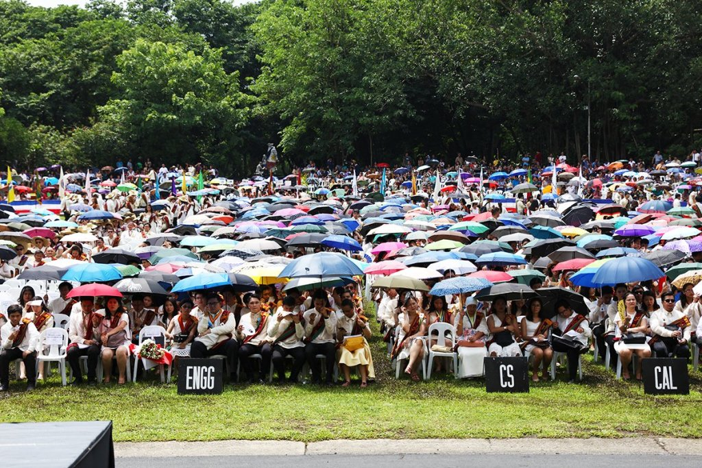 The rows of UP's new graduates turn into a sea of umbrellas as the sun rises to late morning. (Photo by Misael Bacani, UP MPRO)