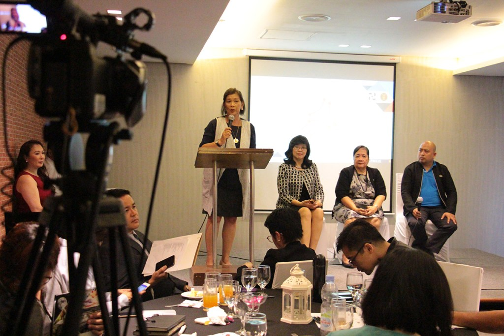 'UP College of Mass Communication Dean Elena Pernia (standing) introduces event speakers (from left) Chancellor Carmencita Padilla, Dr. Laura Pham, and Prof. Louie Balicanta. (Photo by Jun Madrid, UP MPRO)