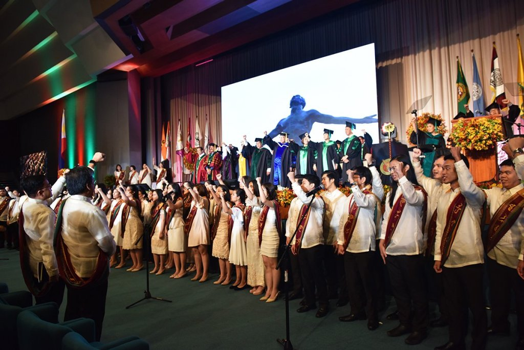 With raised fists, the graduates triumphantly cap the commencement exercises with the singing of the UP Naming Mahal. (Photo by Abraham Arboleda, UP MPRO