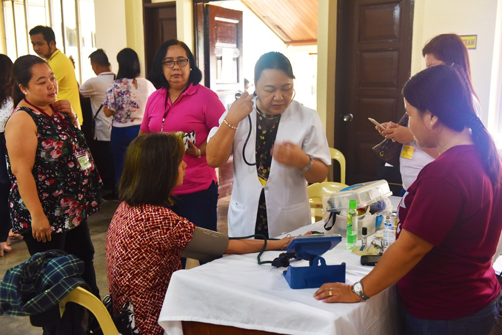A medical team stationed at the registration area checks a participant's blood pressure. (Photo by Bong Arboleda, UP MPRO)