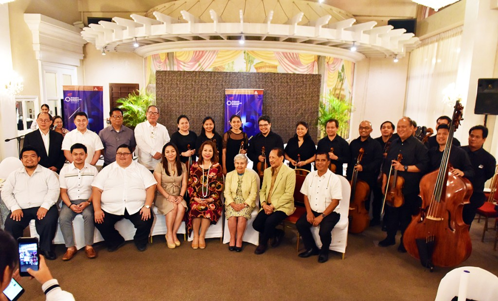 Cultural Center of the Philippines President Arsenio Lizaso (seated second from right), Philippine Philharmonic Orchestra (PPO) conductor Herminigildo Ranera (standing extreme left), members of the orchestra (in black), and partners of the PPO for its outreach performances, which include UP, as represented by Vice President for Public Affairs Jose Dalisay Jr. (standing fourth from left), at the press conference for the PPO's 45th anniversary. (Photo by Bong Arboleda)