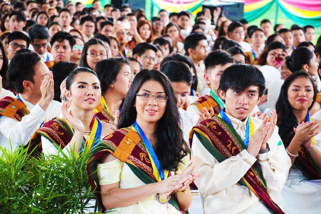 Members of UP Los Baños Class of 2018 applaud as the program for the 46th Commencement Exercises of UPLB begins. (Photo by Jun Madrid, UP MPRO)