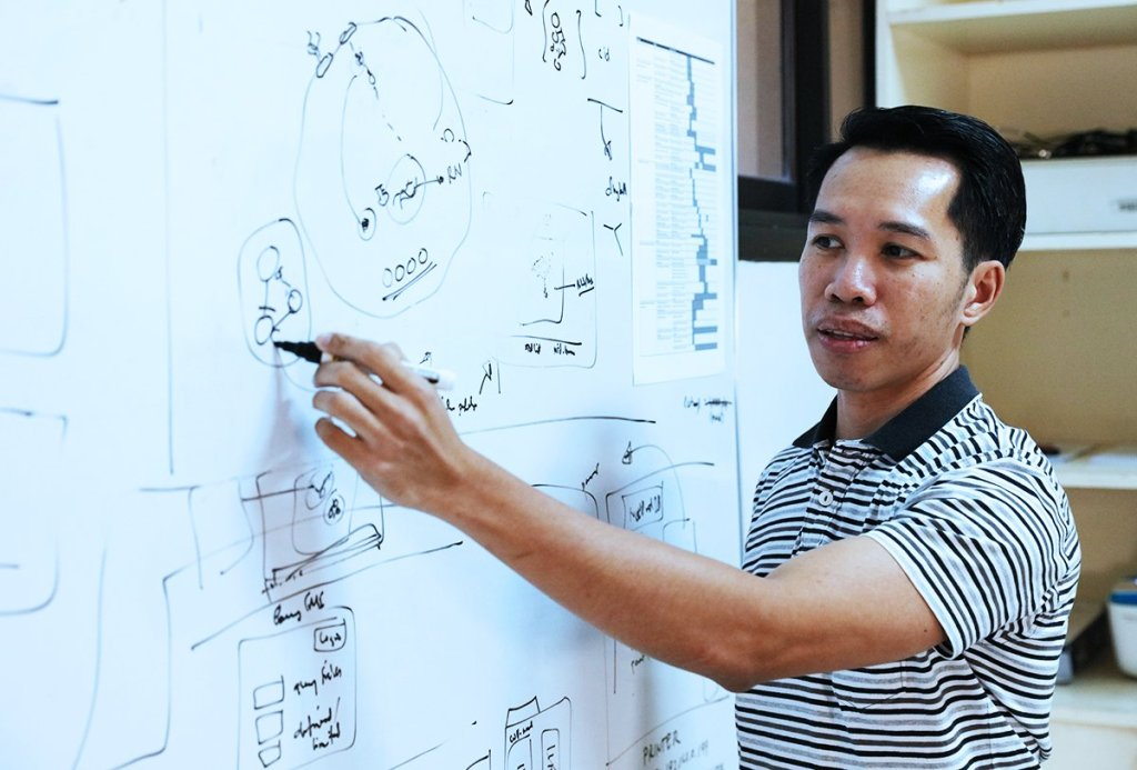 Joeriggo Reyes drawing up the interactions between genes and proteins in cancer. (Photo by El Bacani, UP MPRO)
