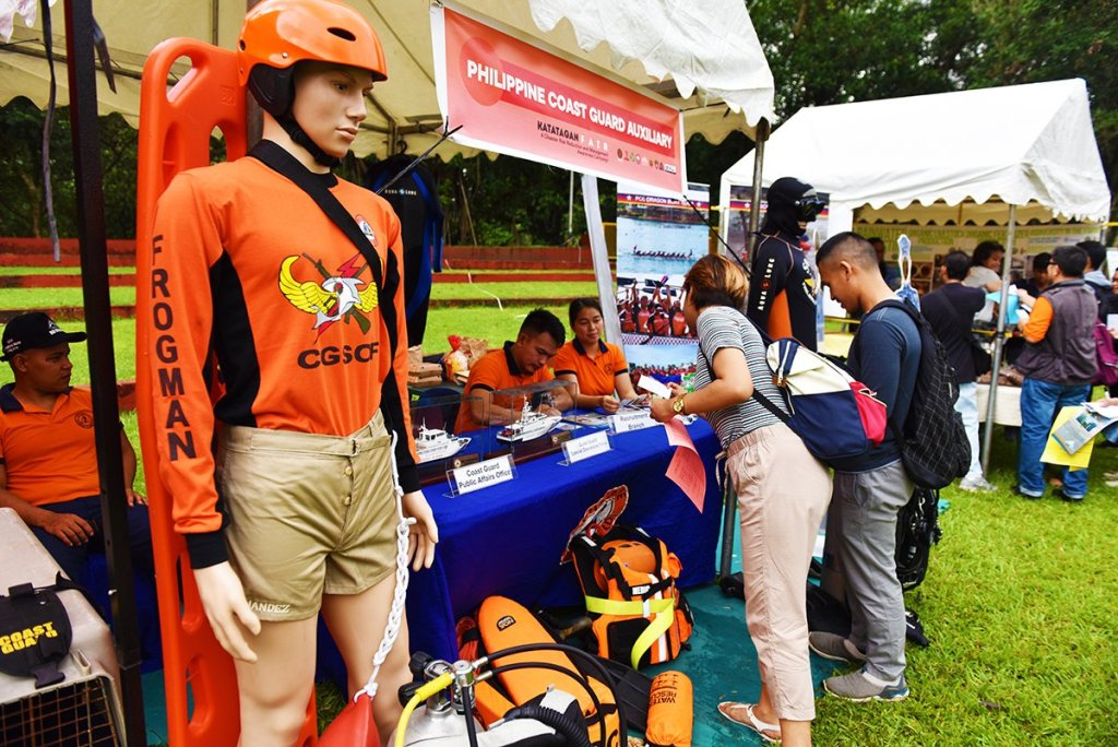 Coast Guard volunteers address inquiry of visitors of their booth. (Photo by Bong Arboleda, UP MPRO)