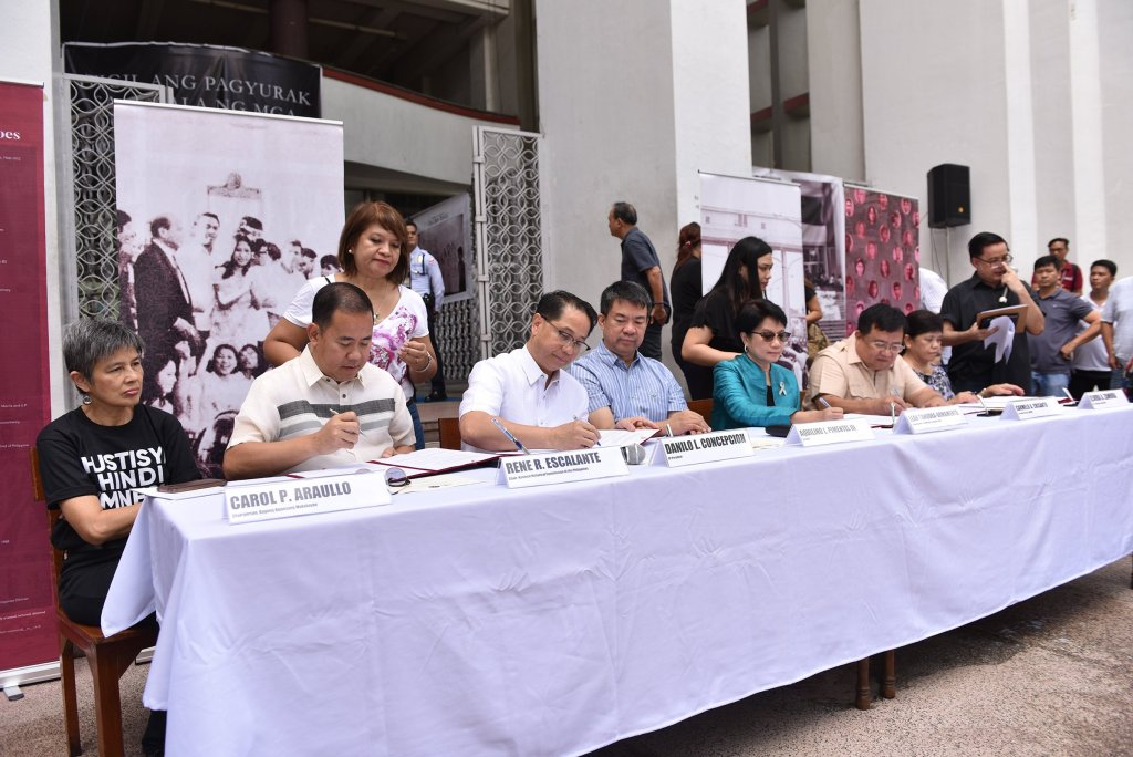 (Left to right) NHCP Chair Rene Escalante, UP President Danilo Concepcion, CHR Commissioner Leah Armamento (representing CHR Chair Chito Gascon), and HRVVMC Executive Director Carmelo Victor Crisanto sign a Memorandum of Understanding for a Human Rights Violations Victims' Memorial in UP Diliman. Dr. Carol Araullo, representing HRVVs; Sen. Aquilino Pimentel III, an advocate of HRRV reparations; and UP Vice President for Development Elvira Zamora are the witnesses. UP Assistant Vice President for Public Affairs (standing) serves as master of ceremonies. Photo by Bong Arboleda, MPRO