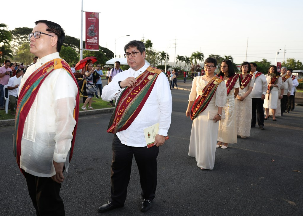 UP officials in the processional: from left, Assistant VP for Public Affairs Jose Wendell Capili, Executive VP Teodoro Herbosa, UP Mindanao Chancellor Sylvia Concepcion, Student Regent Ivy Taroma, Faculty Regent Patricia Arinto, Regent Angelo Jimenez, UPOU University Registrar Aurora Lacaste, UPOU Chancellor Melinda Bandalaria (hidden), Secretary of the University and of the Board of Regents Roberto Lara, and UP President Danilo Concepcion; at the end (hidden) is commencement speaker, CHED OIC J. Prospero de Vera III (Photo by Misael Bacani, UP MPRO)