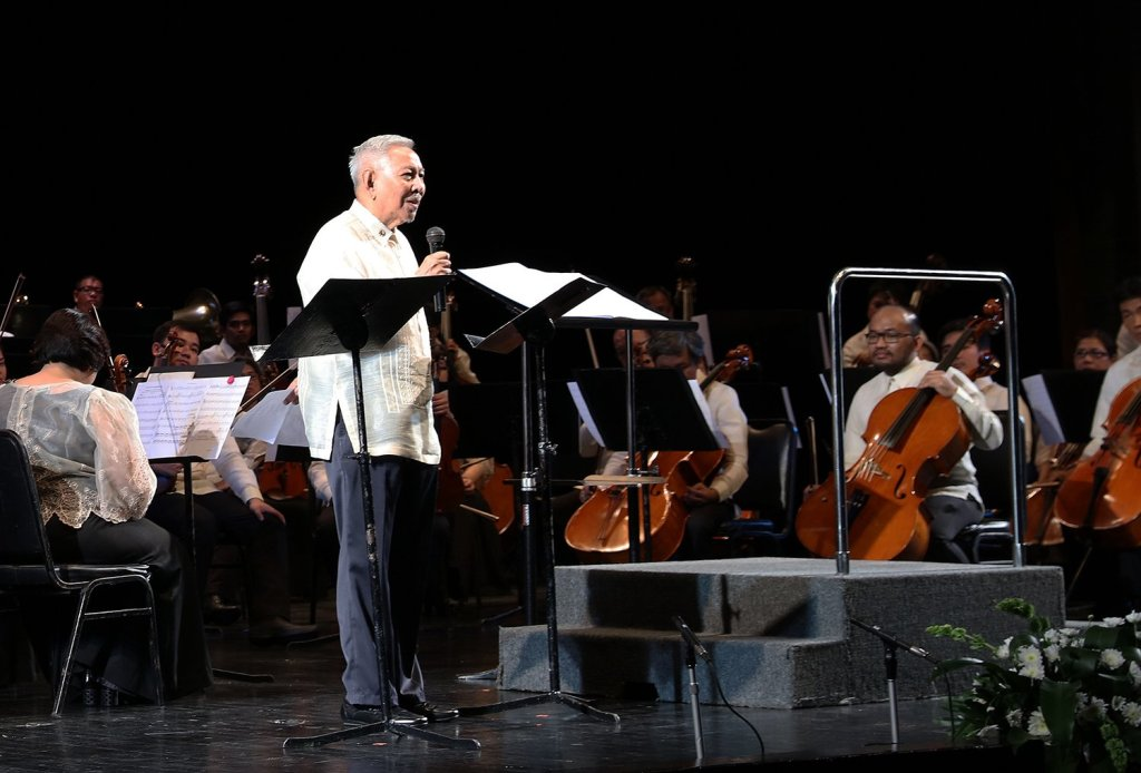 """National Artist for Music and UP University Professor Emeritus Ramon Santos introduces his piece and the concert finale, """"Awit ng Pagdiriwang."""" (Photo by Misael Bacani, UP MPRO)"""
