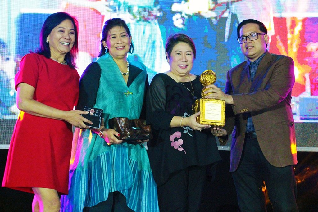 GMA 7's Lilybeth Rasonable (in black) receives her award from the UP CMC Alumni Association's Malou Choa-Fagar, UP CMC Dean Elena Pernia, UP Assistant Vice President for Public Affairs Jose Wendell Capili. (Photo by Jun Madrid, UP MPRO)