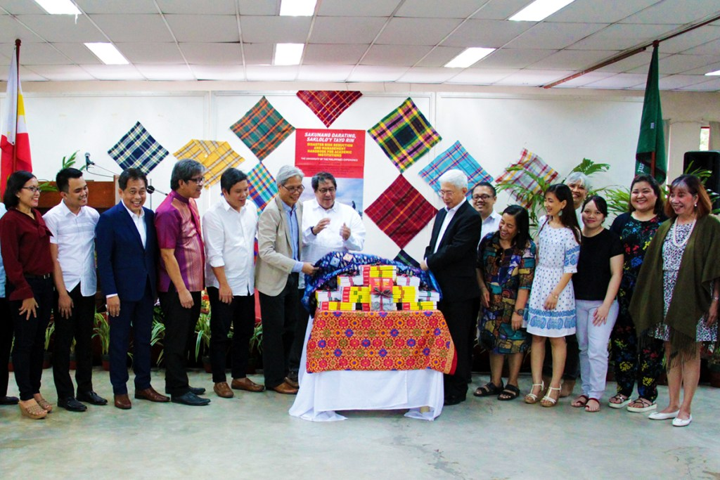 """UP Executive Vice President Teodoro Herbosa (center) and the co-editors and authors of the book, """"Sakunang Darating, Saklolo'y Tayo Rin"""", witness the unveiling ceremony led by Professors Ferdinand Llanes and Alfredo Pascual. (Photo by Jun Madrid, UP MPRO)"""
