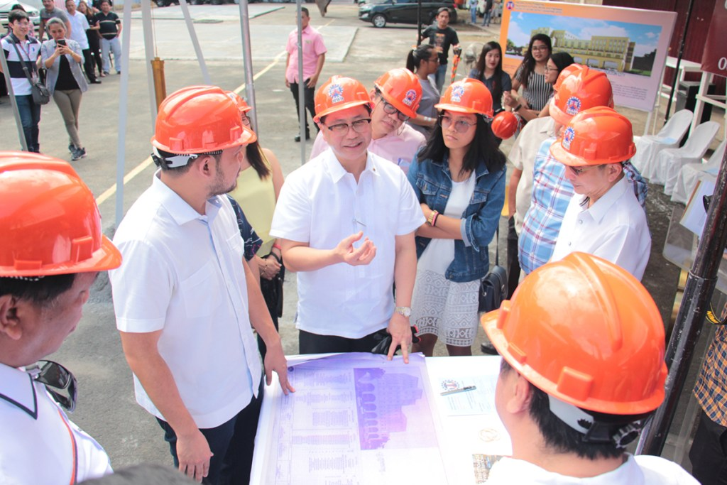 UP and DPWH officials look at the building's blueprint. (Photo by Jun Madrid, UP MPRO)