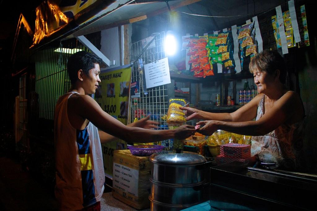 An evening transaction at Bheng's Sari-Sari Store, Barangay Pansol, Quezon City. (Photo by Misael Bacani, UP MPRO)