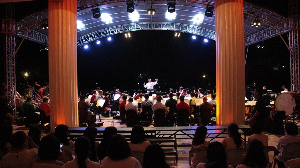 Maestro Herminigildo Ranera conducts the Philippine Philharmonic Orchestra as UP choral groups await the choruses behind the risers. (Photo by Jun Madrid, UP MPRO)