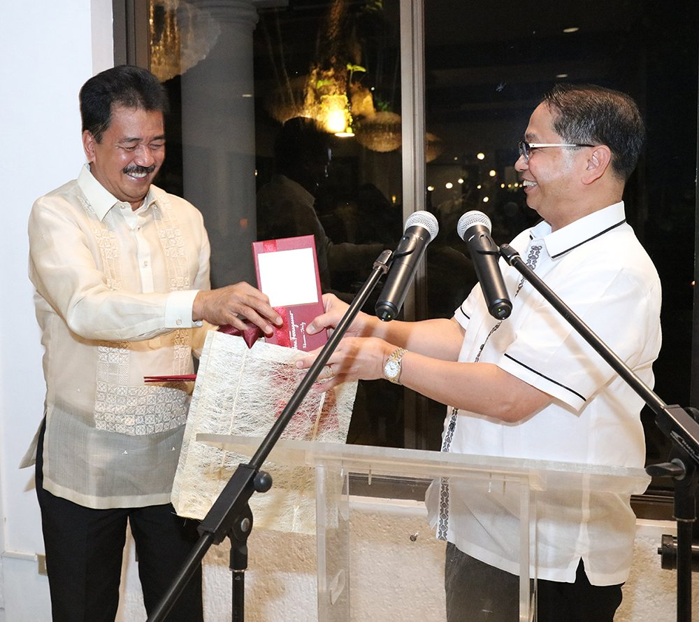 De Vera (left) receives the citation and tokens from UP President Danilo Concepcion. (Photo by Misael Bacani, UP MPRO)