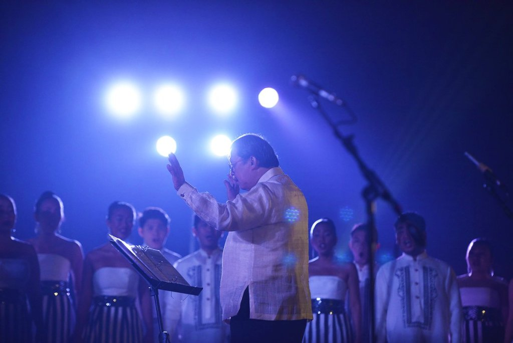 """The UP Singing Ambassador's conductor Ed Manguiat leading the choir during their """"Tunay na Ligaya: A Homecoming and Tribute Concert"""" at the UP Film Center following their triumphant 2018 European tour. (Photo by Noel Ignacio, from the UPSA Facebook page)"""