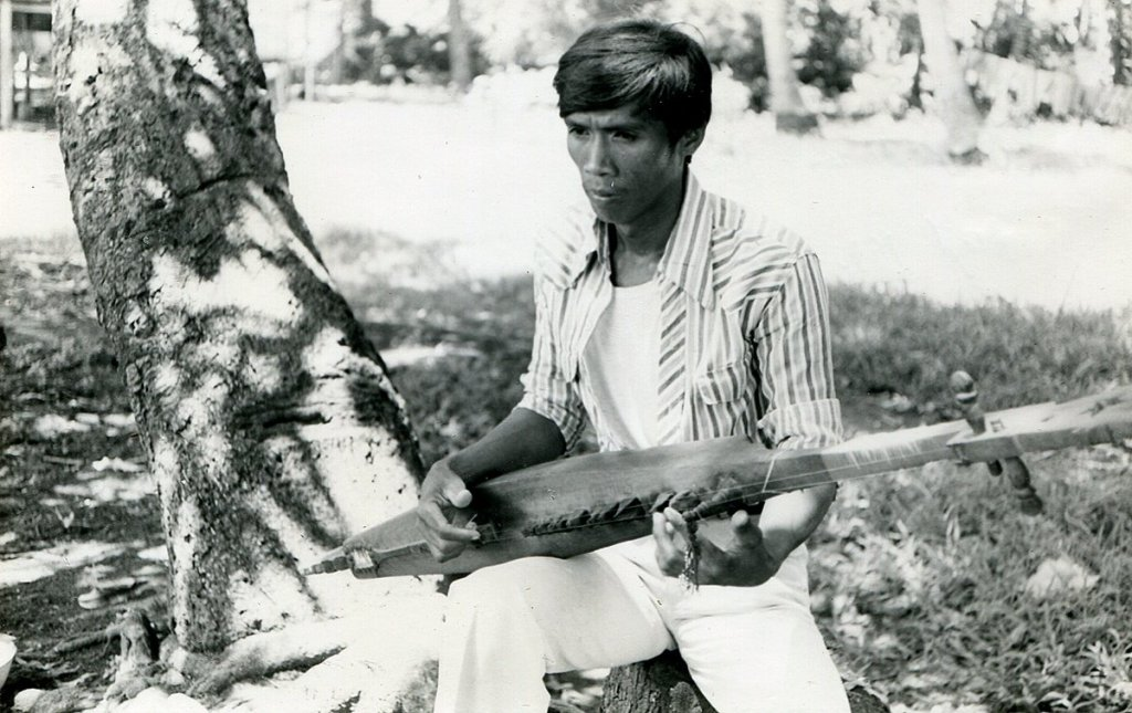 Samaon Sulaiman playing a kutyapi or lute (UPCE-P-5117). Photo from Jose Maceda's research in 1980. Taken from the Jose Maceda Collection of the UP Center for Ethnomusicology.