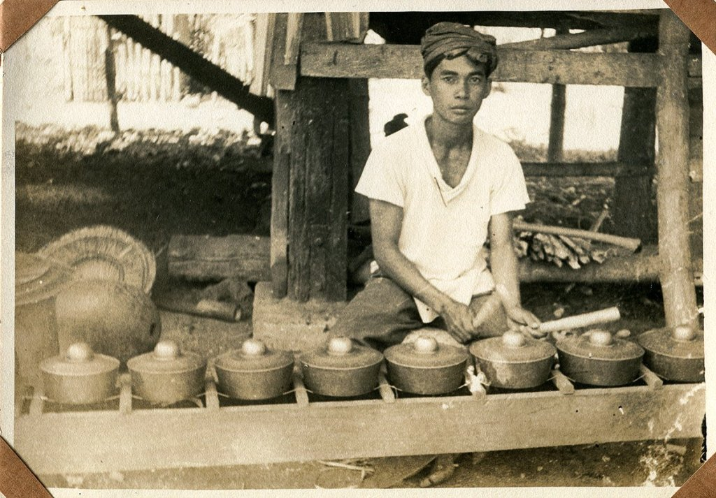 Amal Lumuntud, a kulintang player from Datu Piang, Cotabato, playing the instrument under his house (UPCE-P-2492). Photo from Jose Maceda's research during his 1954 fieldwork among the Maguindanaoans. Taken from the Jose Maceda Collection of the UP Center for Ethnomusicology.
