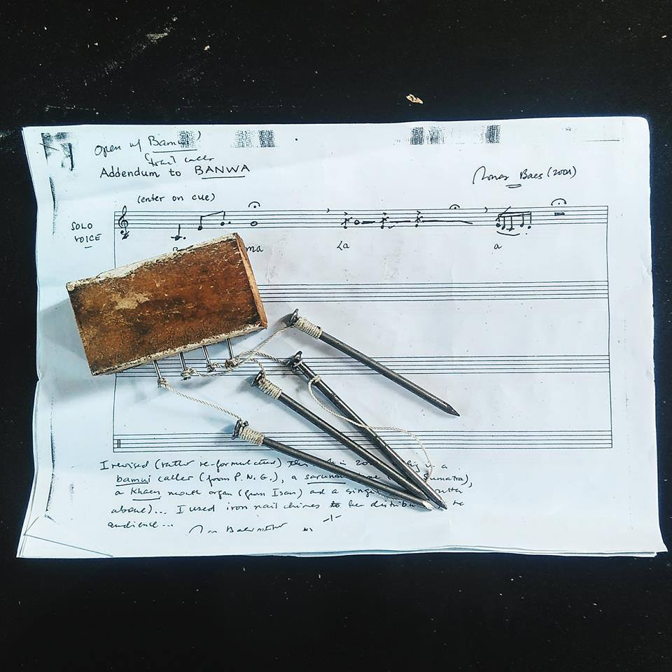 Jonas Baes's iron-nail peace chimes, played by the audience for his 'Patangis-Buwaya' and 'Banwa' compositions to produce subtle glimmering sound like water, over the music sheet for the vocal part of 'Banwa'. (Photo by Gardika Gigih Pradipta, an arts journalist from Indonesia for a workshop of Baes's compositions at the Arts Summit Indonesia in Makassar, Sulawesi in 2016, reproduced with permission from Prof. Baes)