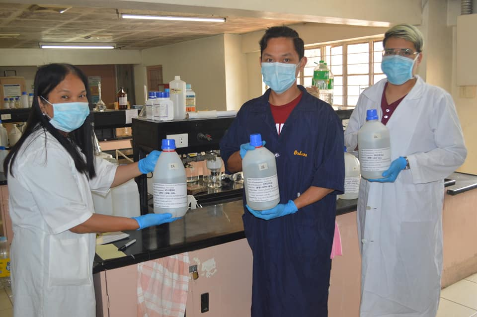 Three members of a UP Baguio team producing 70-percent ethyl alcohol present the finished product straight from the campus laboratories.