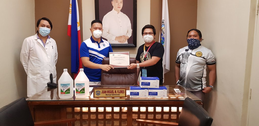 UP Beta Sigma Fraternity, UP Visayas Chapter members Mark Aaron Tinambunan (in black shirt) and Mon Francis Sorongon (in white) donate two gallons of alcohol and three boxes of disposable face masks to the Municipality of Oton. The donation was received by Oton Municipal Administrator Juan Miguel M. Flores.